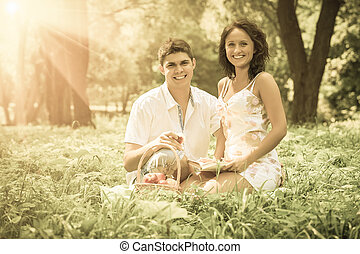 beautiful couple sitting in the grass looking into the camera smiling