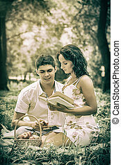 beautiful couple sitting in the grass reading a book