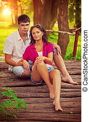 beautiful couple sitting on old wooden bridge and looking at cam