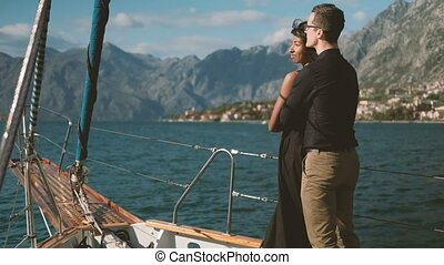 Beautiful couple stand on deck of moving ship in summer.