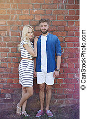 Beautiful couple standing in front of brick wall