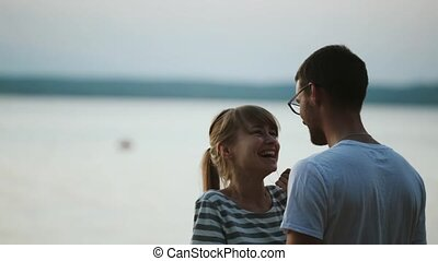 Beautiful couple standing on the shore of the lake and talking. Young couple hugging on the beach on sunset in evening.