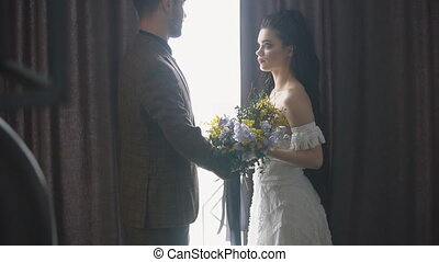 couple stands near the window