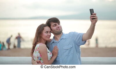 Beautiful couple taking selfie giving kiss on the beach on...