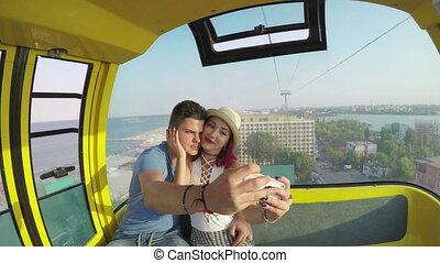 Beautiful couple taking selfie in ropeway