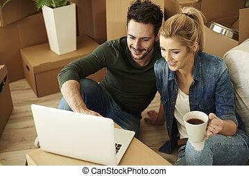 Beautiful couple using laptop among cartons