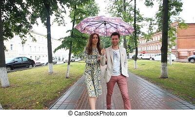 beautiful couple walking under umbrella in park slow