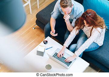 Beautiful couple working on laptop