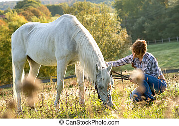 Beautiful cowgirl with her white horse