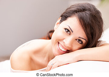 beautiful coy woman smiling on her sofa - beautiful coy...