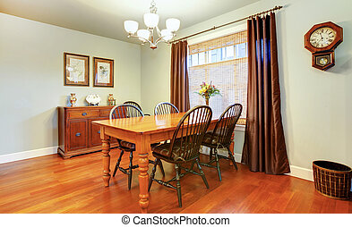 Beautiful cozy dining room decorated with rustic wall clock...