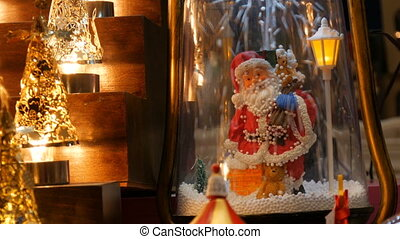 Beautiful cozy luminous Christmas lights and Santa Claus figurine on which artificial snow falls on a market counter