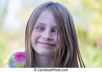 Beautiful cross-eyed young girl outdoors, portrait children...