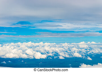 beautiful cumulus clouds and blue sky from the airplane window at high altitude