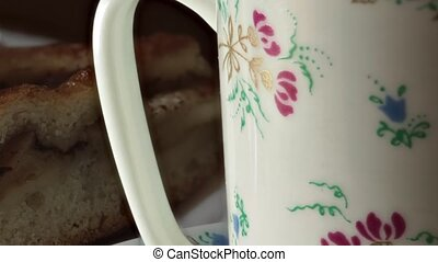 Beautiful cup painted with flowers and a piece of sweet