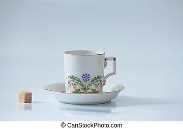 Beautiful cup with flower and piece of sugar