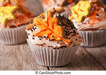 Beautiful cupcakes decorated with autumn leaves close up. horizontal