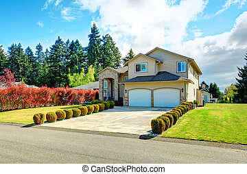Big siding house with garage and high column porch. Green lawn with trimmed hedges and red bushes make the curb appeal stand out