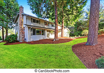 Beautiful curb appeal of two story house with large trees in front.