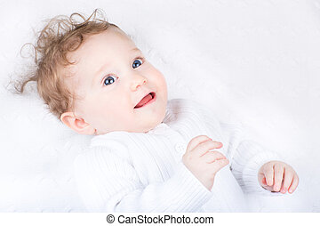 Beautiful curly baby on a white blanket
