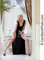 Beautiful curly blonde posing in long black dress