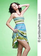 portrait of beautiful curly brunette girl in raise the hem of the summer dress