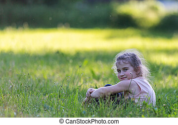 beautiful curly girl sitting in the grass