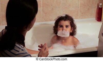 Beautiful curly-haired girl bathing in the bath with foam. Foam on the head. Beard foam. Fun, enthusiasm