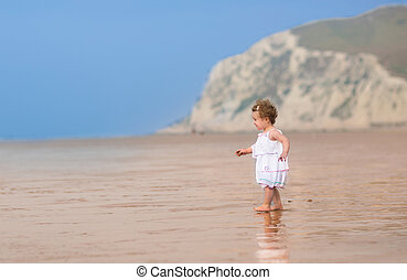 Beautiful curly little girl in a white dress walking on a exotic