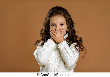 beautiful curly little girl in white sweater asking to be quiet.