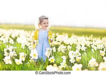 Beautiful curly toddler girl in field