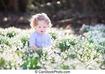 Beautiful curly toddler girl playing with first spring flowers