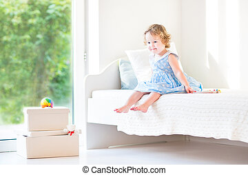 Beautiful curly toddler girl sitting on a white bed next to a bi