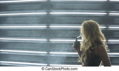 Beautiful curly woman enjoys process of smoking in art studio.