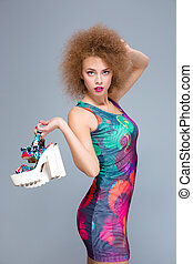 Beautiful curly young female posing with shoes in her hand