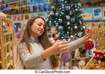 beautiful customer girl choosing Christmas tree decoration...