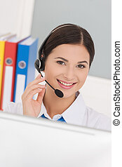 Beautiful customer service representative. Cheerful young female customer service representatives in headset working at the computer and smiling at camera