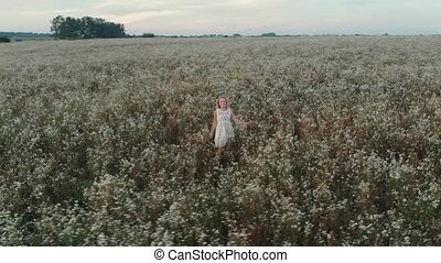 Beautiful cute girl with long hair running in a field with field flowers