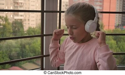 Beautiful cute happy little girl is listening to music on wireless headphones. Funny little girl sings and moves in rhythm. Toddler wearing headphones. Close Home leisure, wireless technology. Slow motion