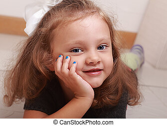Beautiful cute kid girl smiling with manicured finger nails. Closeup portrait