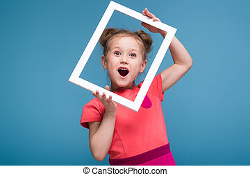 Beautiful cute little girl in pink dress holds picture frame