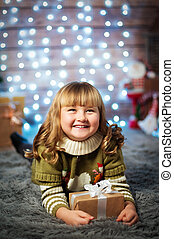 Beautiful cute little girl on christmas background with gift