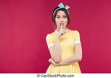 Beautiful cute pinup girl in yellow dress showing silence sign