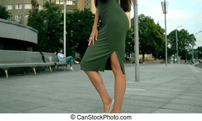 beautiful cute woman in dress stands on a street in the city