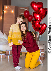 Beautiful cute young brunette mom mother with her teenager handsome boy holding each other and happy together.Woman in yellow pens and red sweeter.