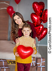 Beautiful cute young brunette mom mother with her teenager handsome boy holding each other and happy together.