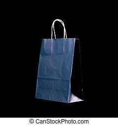 Beautiful dark blue gift bag. Close up. Isolated on black background