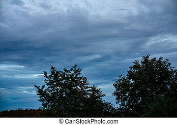 Beautiful dark evening sky with clouds in the village