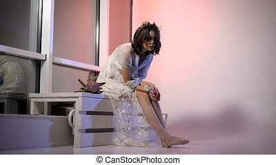 Beautiful dark-haired girl with the image of dead bride in white dress and veil participating in halloween party. Young woman in suit is sitting in the room. Ghost creative scary creepy make-up on the bench bending over her legs strocking them.