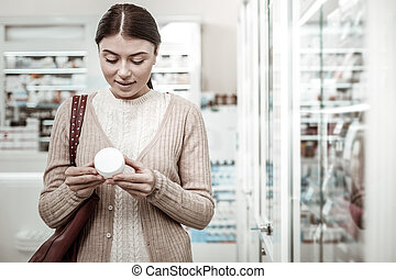 Beautiful dark-haired woman reading contents of face cream standing in drugstore
